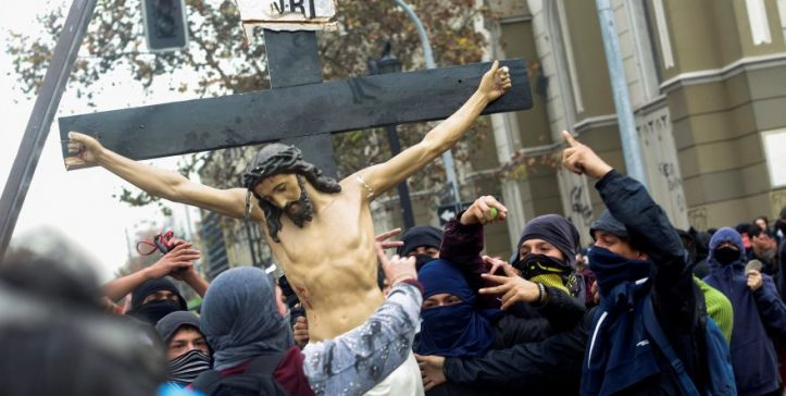 Masked demonstrators carry a cross with Jesus Christ, taken from inside a church during a protest against government education reforms in Santiago, Chile June 9, 2016. REUTERS/Pablo Sanhueza FOR EDITORIAL USE ONLY. NO RESALES. NO ARCHIVE.